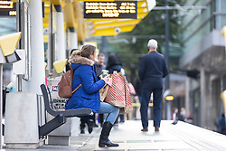 © Licensed to London News Pictures. 02/12/2020. Manchester, UK. A woman sits for the tram with her shopping bags in Manchester as the city enters Tier 3 restrictions.  Photo credit: Kerry Elsworth/LNP