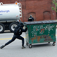 A protester rolls a trash dumpster down Liberty Avenue into police lines in Pittsburgh, Pennsylvania on September 24, 2009.   Pittsburgh is the host city for the two day  G20 Conference.     UPI /Archie Carpenter