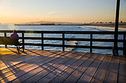 Woman Sitting on a Bench at Seal Beach Pier During Sunset