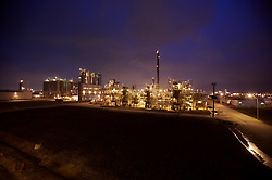 Stock photo of a refinery's structure and piping at night