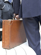 Close up of letter briefcase with two business man talking