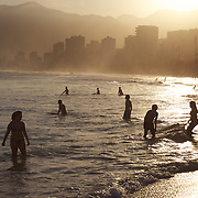 A late afternoon beach scene at Arpoador Beach with Ipanema and Leblon in the distance. Rio de Janeiro, Brazil. 8th August 2010. Photo Tim Clayton..