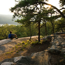 A hiker takes in the views from a ledge populated by pitch pines high above the Connecticut River in Hurd State Park, Haddam, Connecticut.