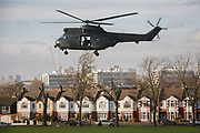 With homes beneath, a Royal Air Force Puma troop-carrying helicopter takes-off again after a brief landing in Ruskin Park in the south London borough of Lambeth. It is believed that the RAF use various public spaces as part of emergency landing/evacuation location familiarisation in readiness of a future national emergency.  The Puma (registration XW216 from 230 Squadron, RAF Benson) is used as battlefield helicopters within the Joint Helicopter Command and provide tactical troop and load movement by day or by night.