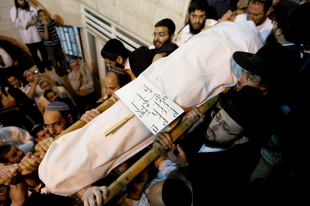 Orthodox Jewish men carry the body of Mordechai Eliyahu, a former Sephardic chief rabbi of Israel and a spiritual leader of the religious Zionist movement, during his funeral in Jerusalem on June 7, 2010. Tens of thousands of faithful took part in the funeral of the rabbi who died at age 81 following a long illness.