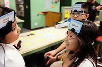 Judith Hernandez, 7, Alfredo Matias, 9, and Esmeralda Matias, 7, play a word-guessing game at the Breadbox Recreation Center in Salinas.