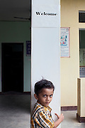 The young nephew of Dr Lenin Raghuvanshi is standing near a Welcome sigh inside the PVCHR headquarters in Varanasi, Uttar Pradesh, India. Lenin's grandfather was a freedom fighter in India's fight against the British. His father was a communist, so he names all of his children after famous communists: Mao, Che Guevara, Stalin, Lenin and Raul. Lenin used to be a doctor in Ayurveda and modern medicine but quit because of the inherent corruption he witnessed. He founded PVCHR in 1996. The charity organises workshops, supports victims during trial and with the police, and promotes education and gender equality.