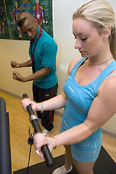Trainer showing woman how to use pull up weights at Southglade Leisure Centre; Nottingham