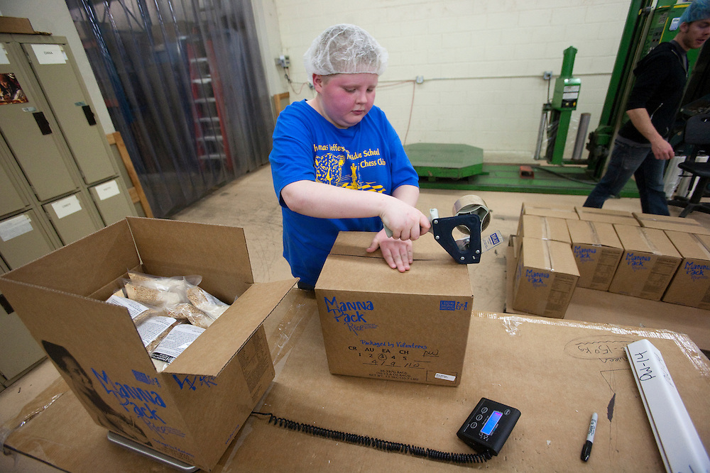 Harold Johnson of Immaculate Conception Parish in Saukville, tapes a box of meals shut after checking it for weight. The boxes are then loaded onto a pallet where they are wrapped and loaded back onto the truck, .Friday, April 9.