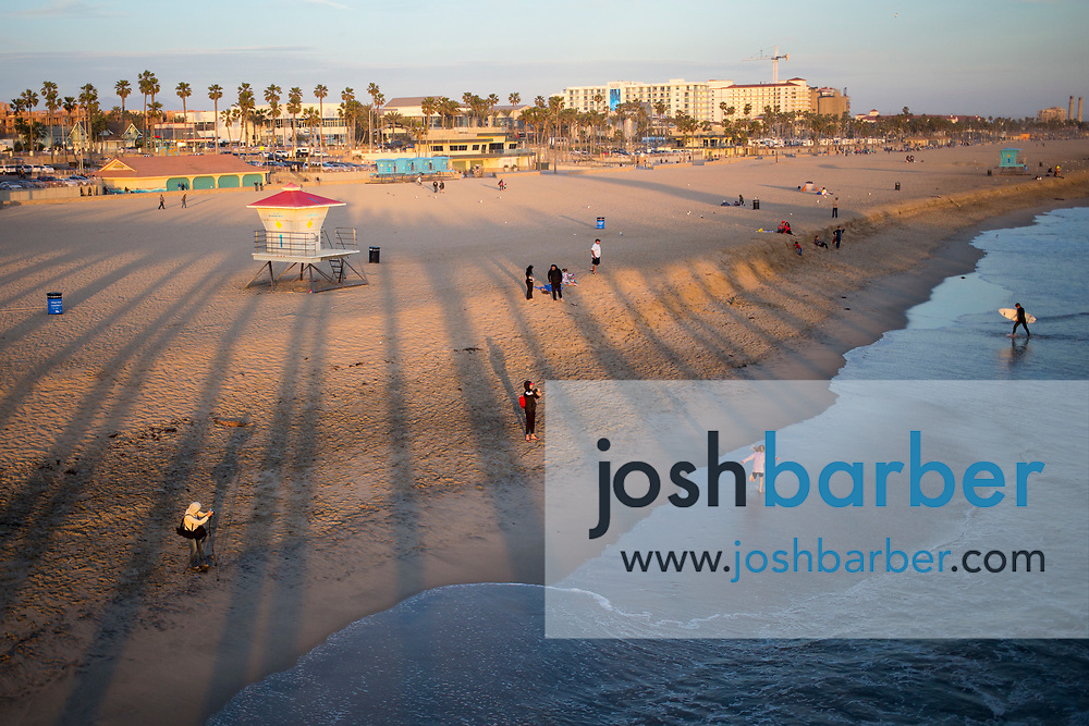 A beach tableau with children playing in the shallows and surfers during sunset at Huntington Beach Pier on Friday, March 24, 2017 in Huntington Beach, California. (Photo/Josh Barber)