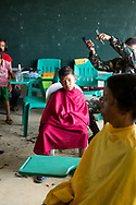 A boy has his hair cut by a member of the Philippine Army at Candalaria National High School during a mobile clinic outreach in the village of Roxas Ocho, Philippines.
