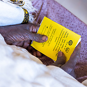 INDIVIDUAL(S) PHOTOGRAPHED: N/A. LOCATION: Mecha Health Center, Bahir Dar, Ethiopia. CAPTION: A patient holds her CBHI card, while being seen by a doctor.