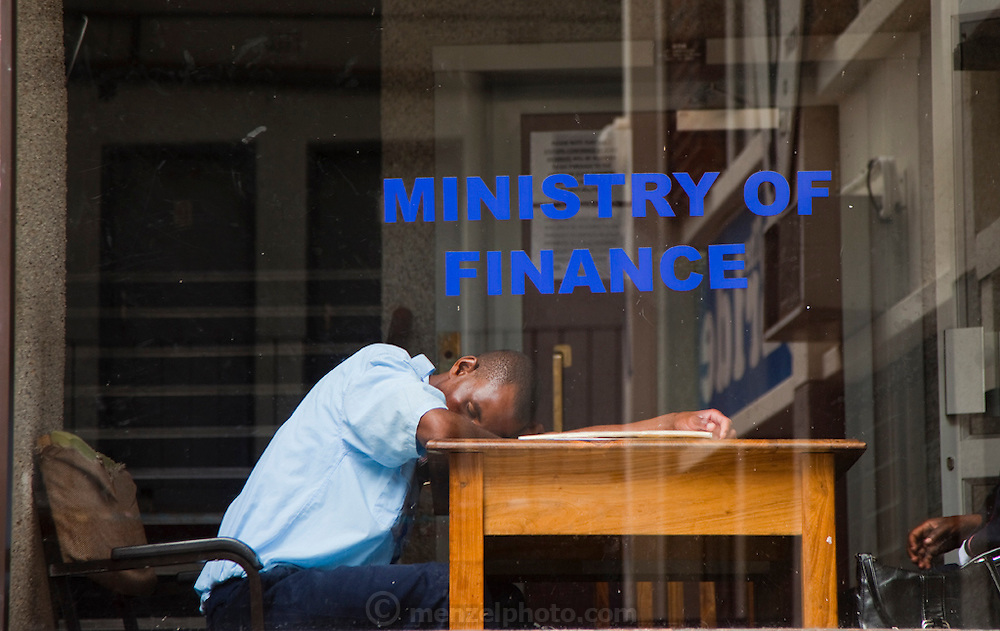 A security officer takes an afternoon nap at the front desk of the Ministry of Finance in Windhoek, Namibia.
