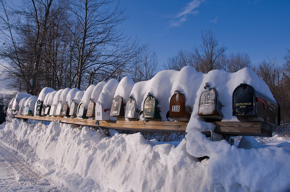 Row of snow covered mailboxes, and snow bank, rural winter scene details, Alexandria, NH