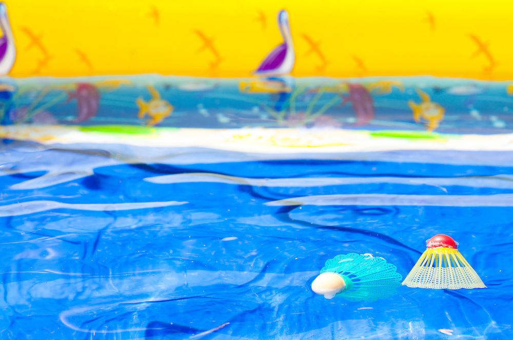 Two badminton shuttlecocks floating in an inflatable swimming pool.