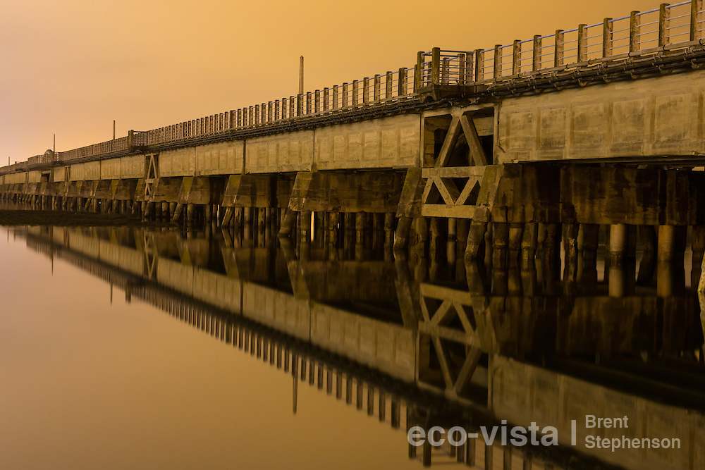 The old, now retired, road and railway bridge that stretches across the channel leading inland from Ahuriri Estuary. Long exposure taken at night in calm and low cloud/mist conditions. Ahuriri Estuary, Napier, New Zealand. September.