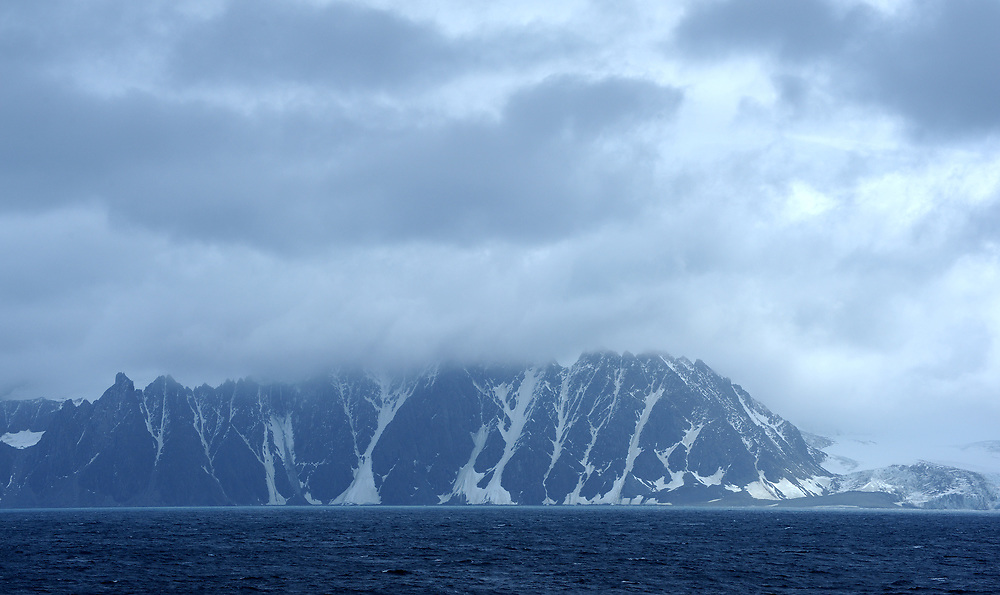 Glaciers and mountains reach down to the sea on Elephant Island. Elephant Island, Antarctica, South Atlantic Ocean. 29Feb16
