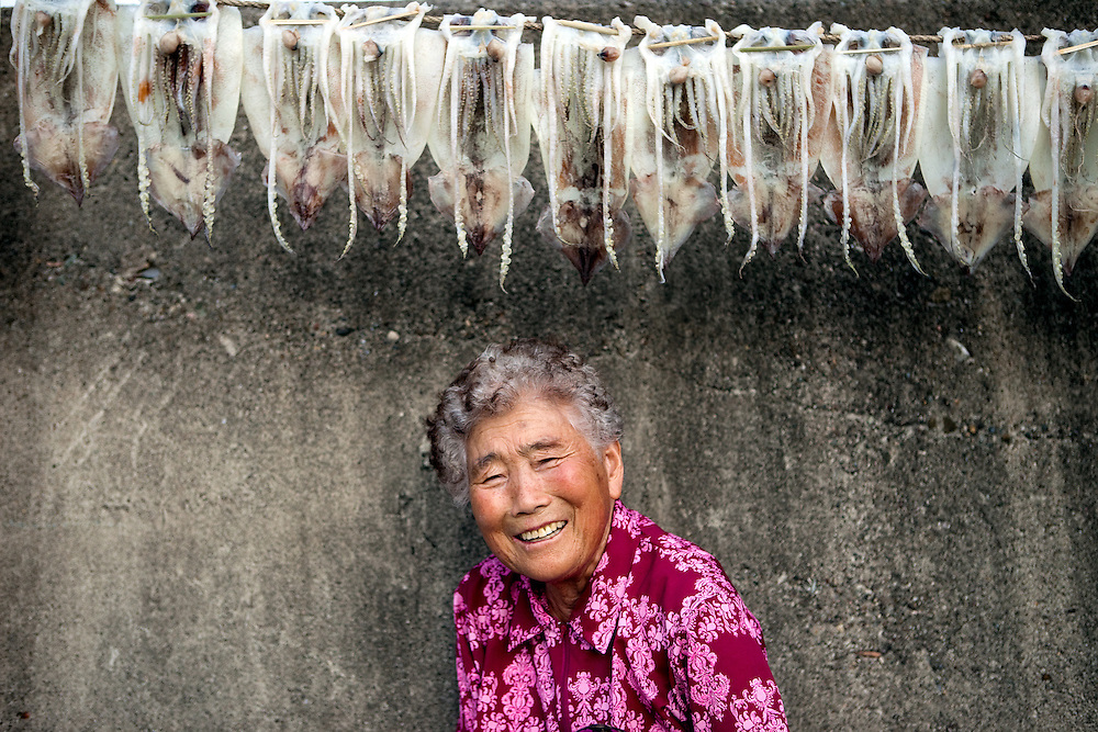 Portrait of the korean village woman labourer sitting under cuttlefish hanging on lines to be dry out / South Korea, Republic of Korea, KOR, 04 October 2009. October 2009.