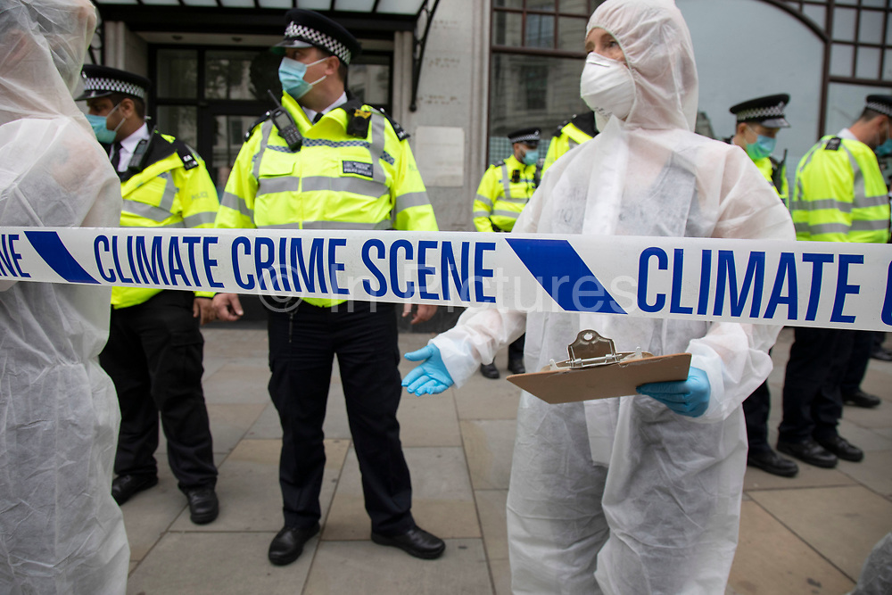 Police lines as Extinction Rebellion 'crime scene investigators' in white suits and masks put up climate crime scene tape to investigate areas of ecocide in a performance outside the Brazilian Embassy on 7th September 2020 in London, United Kingdom. The 20 investigators were protesting at the Brazilian government's alleged involvement in ecocide in the Amazon. Extinction Rebellion is a climate change group started in 2018 and has gained a huge following of people committed to peaceful protests. These protests are highlighting that the government is not doing enough to avoid catastrophic climate change and to demand the government take radical action to save the planet.