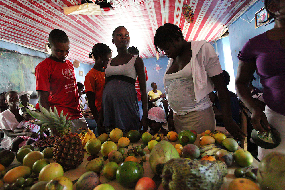A pregnant woman is weighed during a 'Celebration of Life' ceremony in Trou-du-Nord, Haiti.  The 'Celebration of Life' features a weigh-in for all pregnant women and the children that participate in the Pastoral da Criança program to monitor health.  Fresh fruit is laid out on the table in front of the weigh station for people to eat or take home.