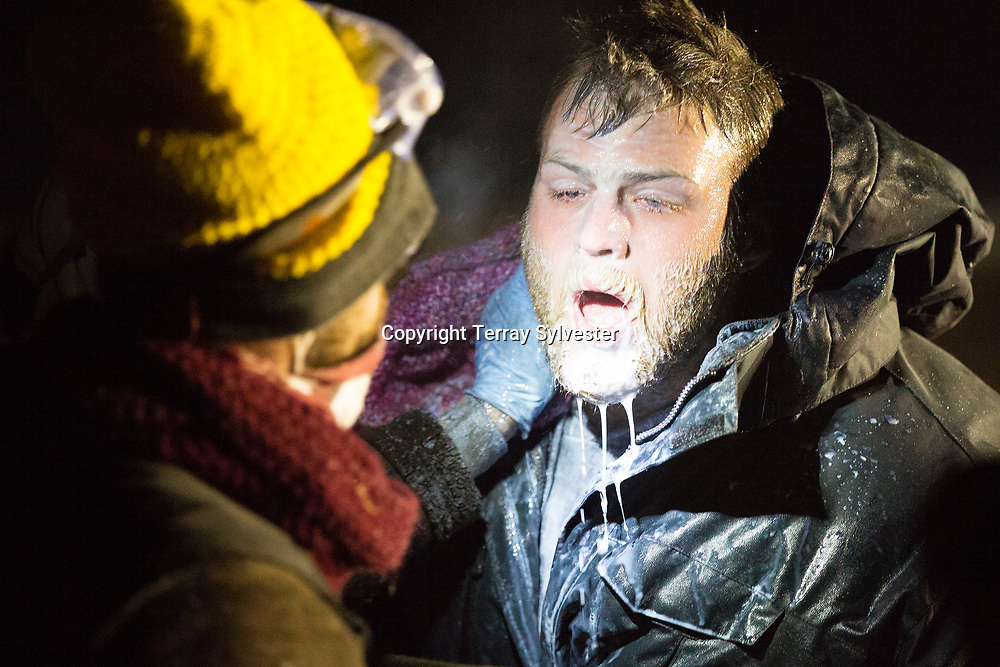 A volunteer medic treats an opponent of the Dakota Access oil pipeline who was exposed to teargas during a standoff with police on Backwater Bridge near the pipeline route on November 20, 2016. Cannon Ball, North Dakota, United States.