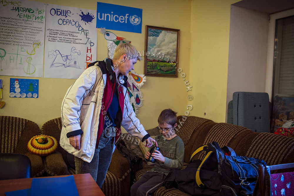 Marina Rassokha, 50, of 'Ukrainian Frontiers', is discussing some video settings with Yaroslav, 10, and his mother Olga, 36, inside a community meeting place in support of internally displaced persons. (IDPs) Yeroslav is taking part to the UNICEF-sponsored One Minute Junior project for internally displaced persons (IDPs), carried out by the local NGO 'Ukrainian Frontiers' in the city of Kharkiv, the country's second-largest, in the east. The conflict between Ukrainian army and Russia-backed separatists nearby, in the Donbass region, have left more than 10000 dead since April 2014, including over 1000 since the shaky Minsk II ceasefire came into effect in February 2015. The approximate number of people displaced by the conflict is 1.4 million as of August 2015. Yeroslav's mother, Olga, is also a participant to a different project of 'Ukrainian Frontiers', called 'Self-Employment', first as a beneficiary, and now as a paid hotline coordinator for people seeking jobs and formation courses.