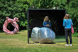 """© Licensed to London News Pictures. 05/07/2017. London, UK. (L to R) """"Fiddlers Fortune"""", 2010, by John Chamberlain and """"Big Be-Hide"""", 2017, by Alicja Kwade.  The Frieze Sculpture festival opens to the public in Regent's Park.  Featuring outdoor works by leading artists from around the world the sculptures are on display from 5 July to 8 October 2017.  Photo credit : Stephen Chung/LNP"""