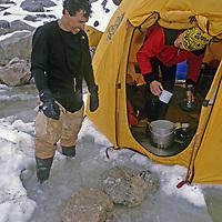 BAFFIN ISLAND, Canada. Greg Child surveys sudden meltwater lake threatening to flood base camp tent during Sail Peak climbing expedition.