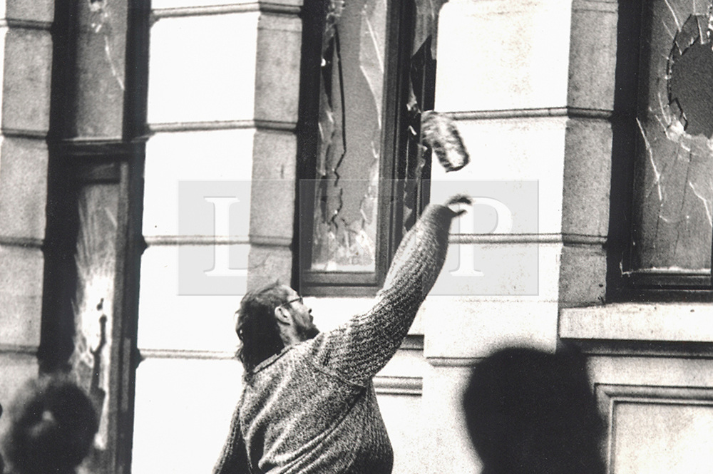 © Licensed to London News Pictures. 25/03/2020. London, UK. In this image from March 31st 1990 a protester throws a brick at the windows of a bank on Charing Cross Road during the London poll tax riots. The protest on the last day of March in 1990 started peacefully when thousands gathered in a south London park to demonstrate against Margaret Thatcher's Government's introduction of the Community Charge - commonly known as the poll tax. Marchers walked to Whitehall and Trafalgar Square where violence broke out with the trouble spreading up through Charring Cross Road and on to the West End. Police estimated that 200,000 people had joined the protest and 339 were arrested. The hated tax was eventually replaced by the Council Tax under John Major's government in 1992.  Photo credit: Peter Macdiarmid/LNP
