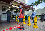 Social distancing is enacted at La Ventanita as patrons wait their turn, six feet apart, to order Cuban coffee and pastries at Cafe Versailles. The popular Cuban restaurant is open for take out service only during the COVID19 pandemic in Miami on Wednesday, April 1, 2020.