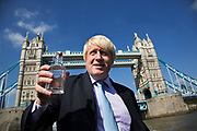 London, UK. Monday 8th September 2014. London Mayor Boris Johnson holding a bottle of water drawn from the source of the Thames with Tower Bridge as the backdrop. The bottle has been carried in Olympic torch fashion by hundreds of people conveying the bottle from the source to the mouth of the Thames. A highlight of Totally Thames, the new month-long promotion of river and riverside events delivered by Thames Festival Trust.