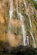 Young woman watches the largest Waterfall along rock vegetation. Plitvicer lake. Croatia. Eastern Europe.