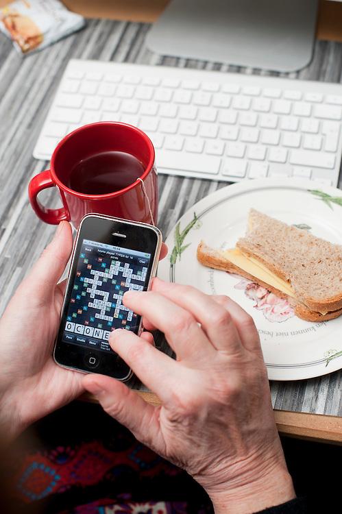 Nederland, Driebergen, 20 nov  2011.Eten op de werkplek en tegelijkertijd een spelletje op de iphone..Foto(c): Michiel Wijnbergh