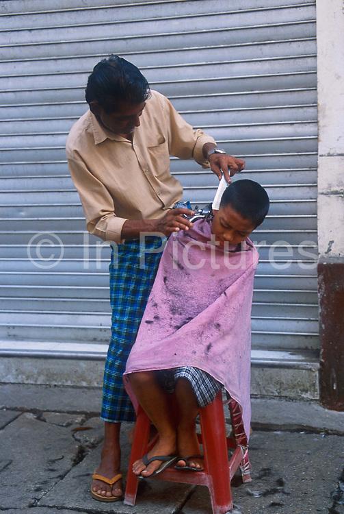 Street barber cutting small boy's hair. Rangoon, Burma 2001