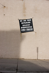 A sign placed at an angle on a stucco wall declaring new car and truck services provided by an mechanic's shop