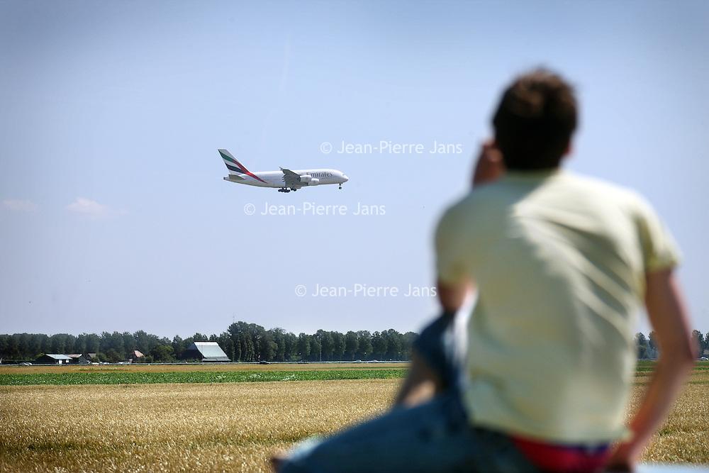 Nederland, Zwanenburg , 1 augustus 2012..De Airbus A380, het grootste passagiersvliegtuig ter wereld, landde vandaag voor het eerst in Nederland met passagiers aan boord..Op de IJweg bij Zwanenburg wachten vele vliegtuigspotters vergeefs lang de Polderbaan. De Airbus zou uiteindelijk tot frustratie van de vele vliegtuigspotters die langs de Polderbaan wachten op een andere baan landen..Op de foto: 1 van de weinige spotters op een andere plek aan de Polderbaan spot de Airbus uit Dubai..Foto:Jean-Pierre Jans