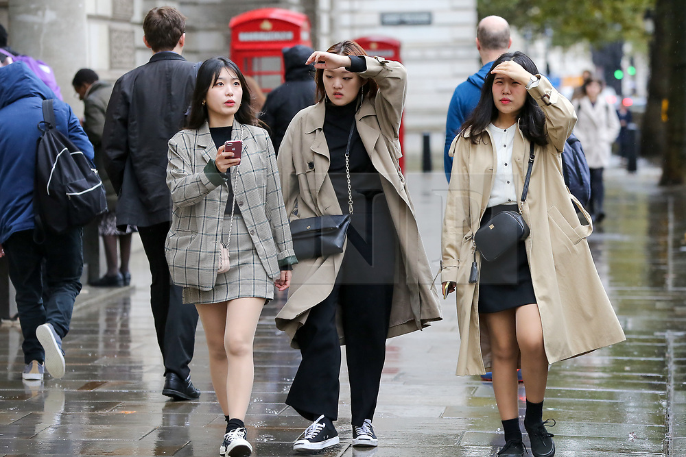 © Licensed to London News Pictures. 16/10/2019. London, UK. Tourists cover their heads with their hands on Whitehall, Westminster. According to the Met Office more rain is forecasted for the next few days. Photo credit: Dinendra Haria/LNP