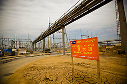 """A """"Guangxi Road"""" sign, referring to the Chinese province that .most of the workers call home stands at the Haiphong Thermal Power Plant construction site in Trung Son, Vietnam, Nov. 22, 2009. Dongfang Electric, a large Chinese contractor, and Marubeni, a Japanese company, won the $500-million contract in 2005. China, famous for its export of cheap goods, is increasingly known around the world for shipping out cheap labor."""