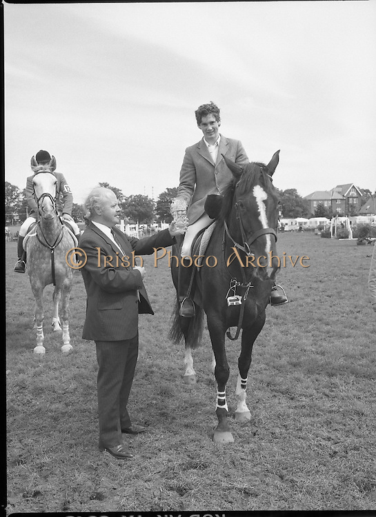 Guinness Competitions At The RDS Horse Show.(R39)..1986..09.08.1986..08.09.1986..9th August 1986..At the Dublin Horse Show at the RDS, Guinness sponsor several events,The Guinness Match International, The Novice Championship and the Guinness Tankard...Image of Mr Dick Frost,Guinness Group Sales, presenting the Novice Trophy to Stephen Smyth aboard 'Hilton Nelly'. Stephen hails from Omagh in Co Tyrone.