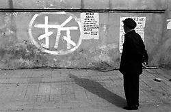 "Man looking at sign painted on wall saying ""Demolish"" in a Beijing hutong"