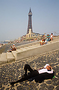 A man dressed in a dark suit and tie, shoes and socks lies down on his matching jacket for a short rest - perhaps during a lunchtime break from an office job - and stretches out on the incline of Blackpool seafront. In the background is Blackpool Tower, an architectural copy of Paris' Eiffel Tower opened to the public on 14 May 1894 and rises to 158m (518 ft 9 inches). As a sort of English eccentric character, the man looks incongruous as he sleeps in sunshine amid other holidaymakers. This northern seaside resort in the north-west of England is diverse in its transient holiday population whose behaviour can be routinely odd. Blackpool is the largest resort in the north of England and visited traditionally by working people from industrial towns and cities during the industrial revolution.