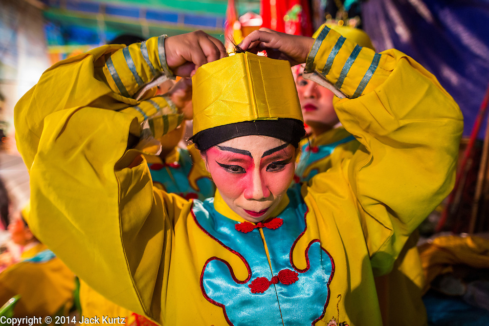 """25 JANUARY 2014 - BANG LUANG, NAKHON PATHOM, THAILAND: Performers get into character for a Chinese opera performance in a small town near Bang Luang, Nakhon Pathom, Thailand. Chinese opera was once very popular in Thailand, where it is called """"Ngiew."""" It is usually performed in the Teochew language. Millions of Chinese emigrated to Thailand (then Siam) in the 18th and 19th centuries and brought their cultural practices with them. Recently the popularity of ngiew has faded as people turn to performances of opera on DVD or movies. There are still as many 30 Chinese opera troupes left in Bangkok and its environs. They are especially busy during Chinese New Year when travel from Chinese temple to Chinese temple performing on stages they put up in streets near the temple, sometimes sleeping on hammocks they sling under their stage.     PHOTO BY JACK KURTZ"""