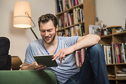 Mid adult man using digital tablet in living room and smiling, Munich, Bavaria, Germany