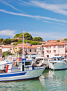 Boats and yachts moored in the harbour of the small, Tuscan town of Talamone, on the coast of the Mediterranean sea in Italy