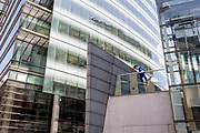 Beneath the architicture of modern corporate offices, a runner stretches his knee joints and muscles on the first level of a walkway at Broadgate in the City of London, the capital's financial district - aka the Square Mile, on 29th July 2019, in London, England.
