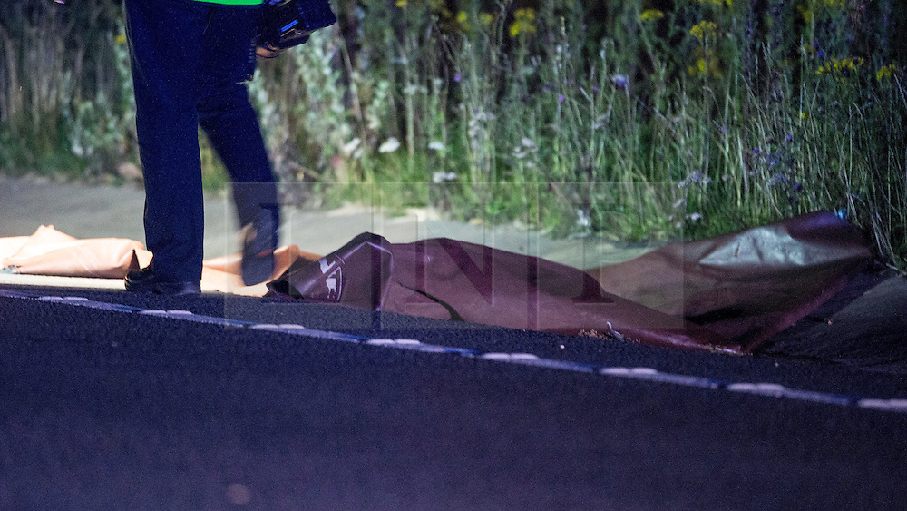 © Licensed to London News Pictures . 21/07/2014 . Nottinghamshire , UK . Police examine what appears to be a tarpaulin on the side of a slip road , adjacent to the accident scene . Police , fire crew and ambulances on the A1 road in Ranby yesterday morning (21st July 2014) following a fatal multi vehicle accident . Leroy and Sheila Carrington (aged 68 and 58) died at the scene when the Peugot 206 they were driving collided with a Vauxhall Astra . Roderick Franks (58) , who was a passenger in the Astra , died in hospital , following the crash . The road was closed in both directions whilst police investigated the scene .  Photo credit : Joel Goodman/LNP