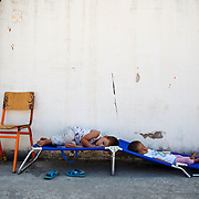 Two Afghan children nap in a shady spot during the mid-day summer heat in Oinofyta refugee camp, Greece, July, 2016.