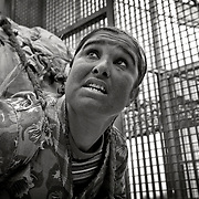 """MELILLA, SPAIN - APRIL 20, 2010 :  A woman porter carrying  contraband goods up to 80 kg.or more in weight passing  through """" the cage """"  at the border of  El Barrio Chino on April 20 , 2010 in Melilla. Spain. Every day at the pedestrian border of El Barrio Chino hundreds of people are involved in transporting smuggled goods from Melilla a Spanish enclave on the North African coast to Morocco.For each package introduced in morocco receive between 3 an 5 euros depending on size,with a little luck achieved make three trips a day.It is estimated that from Monday to Thursday on foot enter Melilla 8.000 porters, mostly women, to return to Morocco with huge sacks of goods from the warehouse border area of Beni Enzar in Melilla .<br /> ( Photo by Jordi Cami )"""