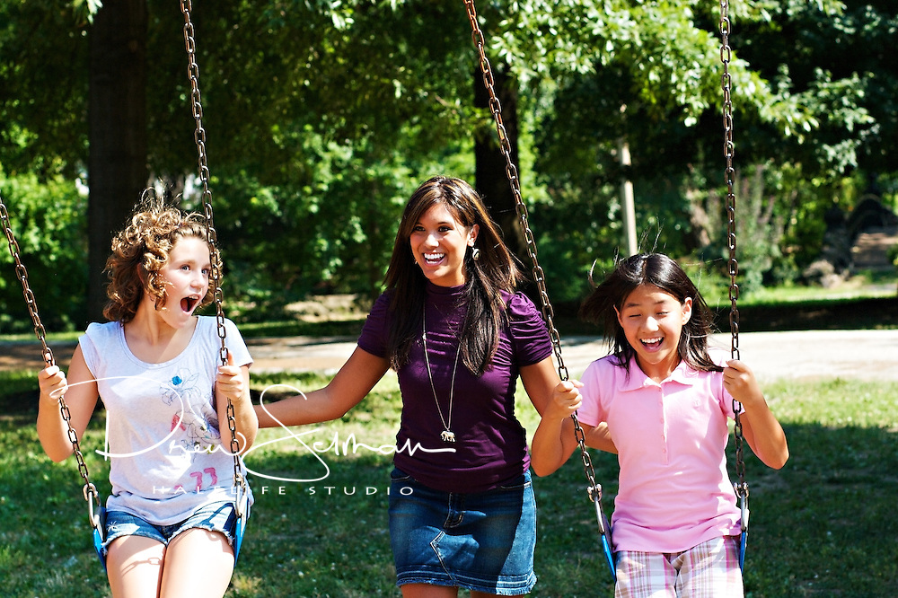 Two mixed race teenagers (Caucasian and Asian)swing in a park on a sunny, summer afternoon while being pushed by a young Asian female woman