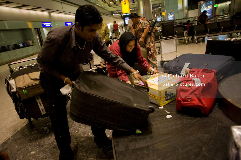 """A family just arrived from Chennai (India) drags heavy suitcases from the carousel in the arrivals of Heathrow Airport's Terminal 5. 50-70,000 pieces of British Airways baggage a day travel through 11 miles of conveyor belts which were installed in a 5-storey underground hall beneath the 400m (a quarter of a mile) length of Terminal 5. T5 alone has the capacity to serve around 30 million passengers a year and was completed in 2008 at a cost of £4.3bn. The system was designed by an integrated team from the airport operator BAA, BA and Vanderlande Industries of the Netherlands, and handles both intra-terminal and inter-terminal luggage. From writer Alain de Botton's book project """"A Week at the Airport: A Heathrow Diary"""" (2009)."""